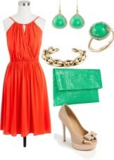 Coral-värinen mekko yhdessä vihreiden lisävarusteiden kanssa