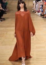 Pitkä pörröinen terrakotta-mekko, joka on valmistettu läpikuultavasta kankaasta