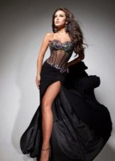 The dress is black with a transparent corset and rhinestones.