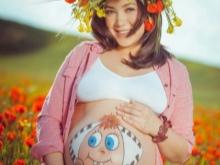 Lichaamsschildering op de buik van een zwangere vrouw - een kind Alenka