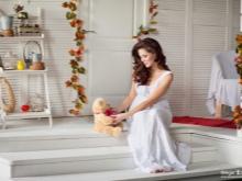 Zwanger met een zacht stuk speelgoed in een fotostudio