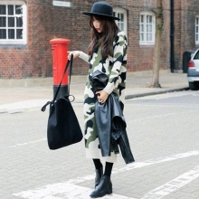 Bir şapka, çanta ve siyah ceket ile kamuflaj elbise