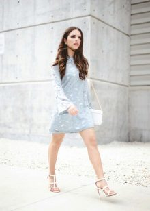 Bolsa branca e sandálias em combinação com um vestido azul