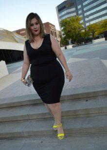 Zwarte jurk voor volledige meisjes in combinatie met gele sandalen