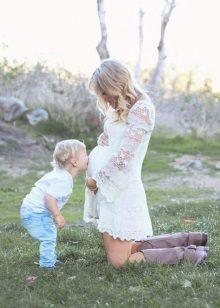 Witte jurk voor een fotosessie zwanger - zoon kust zijn buik