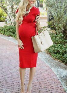 Червена рокля за бременни жени в комбинация с бежови обувки и чанта