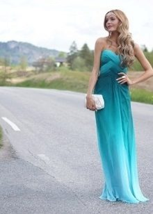 Evening gown of aqua color with the transition to blue