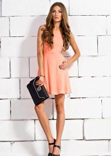 Persikka lyhyt mekko, jossa on mustat tarvikkeet
