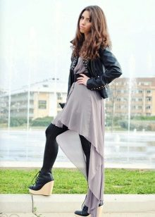 Asymmetrical dress in combination with a leather jacket and tight tights.