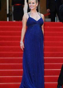 Lange blauwe jurk op de vloer op de tinten met een hoge taille voor zwangere vrouwen