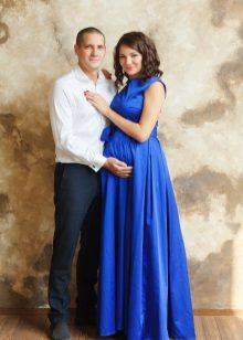 Fotoshoot voor een zwangere vrouw in een blauwe lange jurk