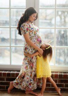 Fotoshoot voor een zwangere vrouw in een lange jurk met een bloemenprint