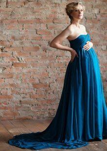 Blauwe jurk met een trein voor een zwangere fotoshoot
