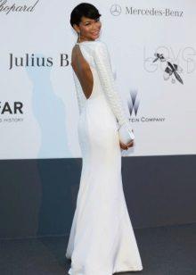 Pitkä valkoinen mekko, jossa pitkät hihat ja avoin selkä