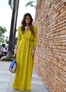 Pitkä keltainen mekko, jossa pitkät hihat