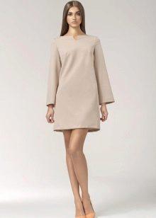Um vestido bege curto inspirado nos anos 60 com mangas compridas e um par de bombas.