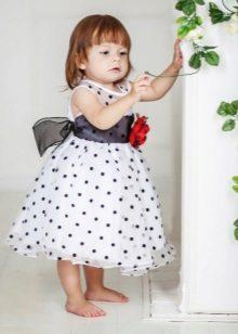 Vestido elegante para a menina branca em ervilhas pretas