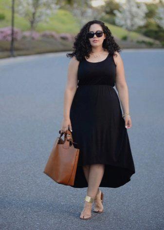 Zwarte jurk met een asymmetrische rok voor vol in combinatie met gouden sandalen en een bruine tas
