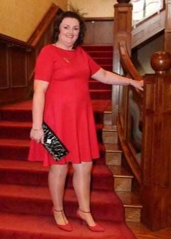 Rode jurk voor zwaarlijvige vrouwen met rode schoenen en zwarte clutch