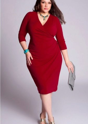 Dikke vrouw in een rode jurk met een grijze clutch en gouden sandalen