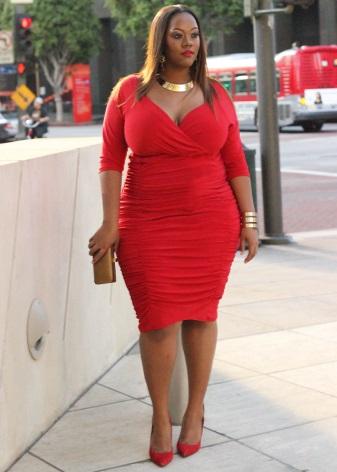 Rode jurk voor zwaarlijvige vrouwen met rode schoenen en gouden accessoires