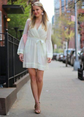 Pembe bir çanta ve küpeler ile birlikte kısa süt elbise