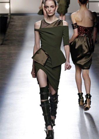 Epäsymmetrinen sotilaallisen tyylin mekko, jossa on korkeat saappaat vyöllä