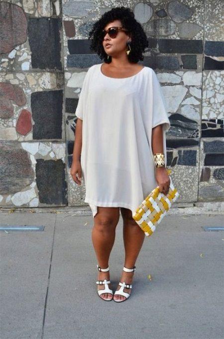 Vestit blanc-túnica per a dones obeses en combinació amb sandàlies blanques i accessoris d'or