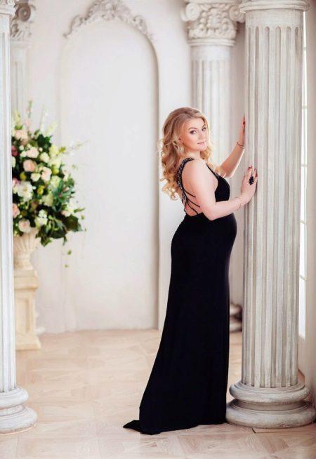 Fotoshoot voor een zwangere vrouw in een zwarte lange jurk