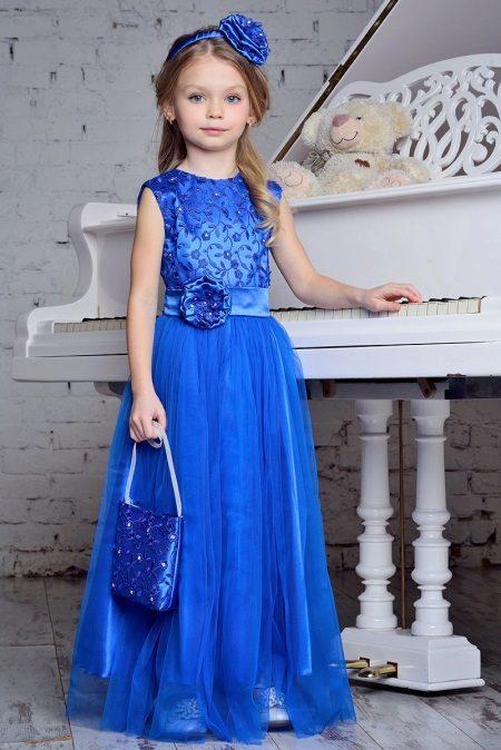 Vestido elegante em um piso azul para a menina