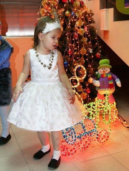 Vestido de ano novo o floco de neve com uma decoração para a menina